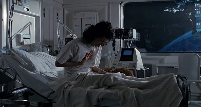 Image of Ripley clutching chest in hospital room